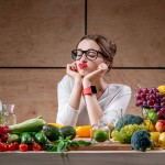 Young and sad woman thinking about tasty food and calories sitting at the table full of fruits and vegetables in the wooden interior.